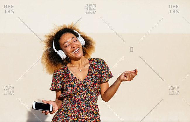 Woman with afro hairstyle dancing listening music on phone.