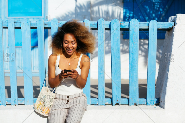 Woman with afro hairstyle using her phone on beach promenade.