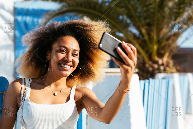 Woman with afro hairstyle taking a selfie on beach promenade in summer.