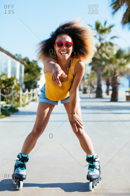 Woman with afro hairstyle roller skating on footpath during sunny day.