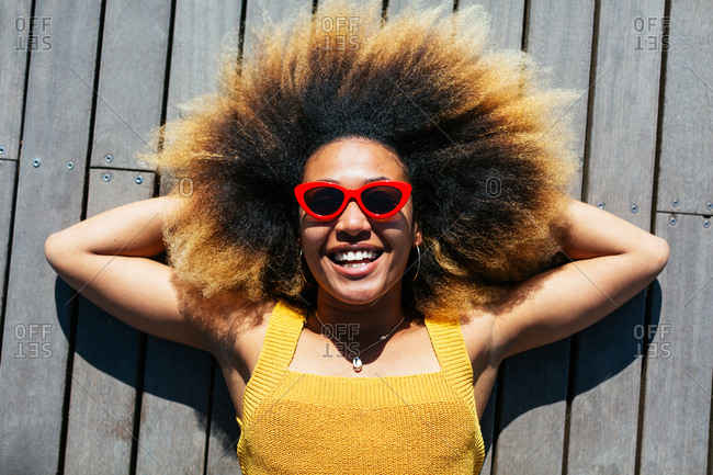 Overhead of a smiling woman with afro hairstyle sunbathing.
