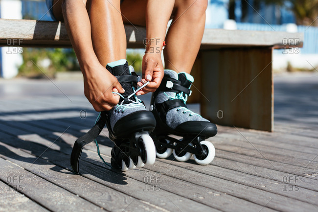 Anonymous woman wearing roller skate sitting on footpath in summer.