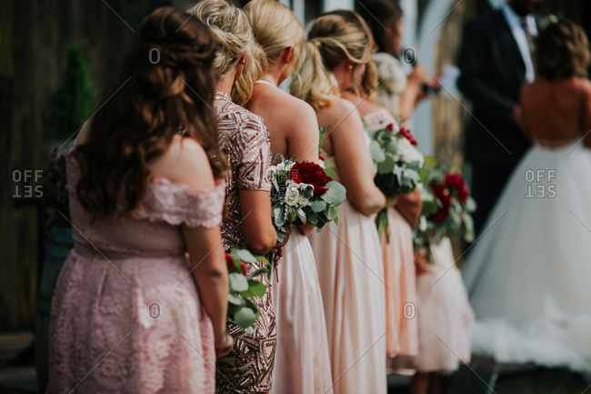 Young girls helping bride with her dress