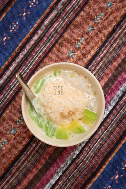 Asian dessert with rice, sweet coconut milk, ice, tapioca balls and melon
