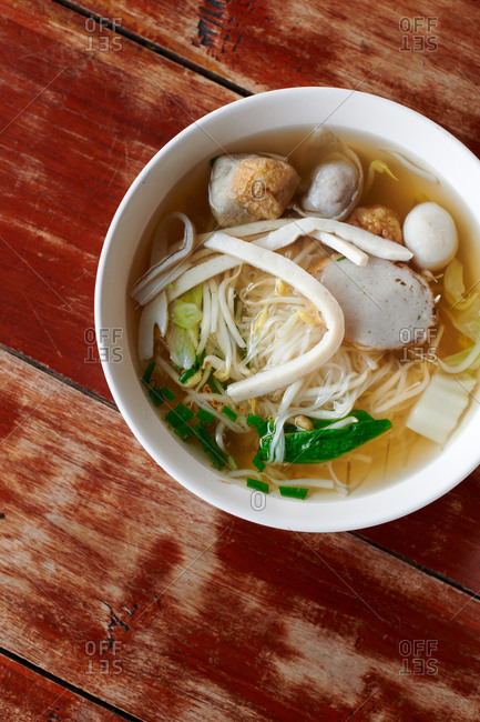 Bowl of fish ball and fish cake noodle soup with a clear clean broth