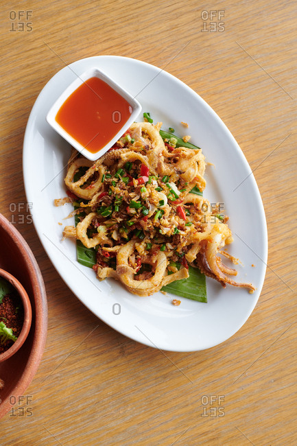 A dish of fried Calamari with a sweet chili dipping sauce on a wooden table