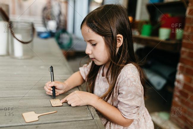 Little girl writing labels for garden