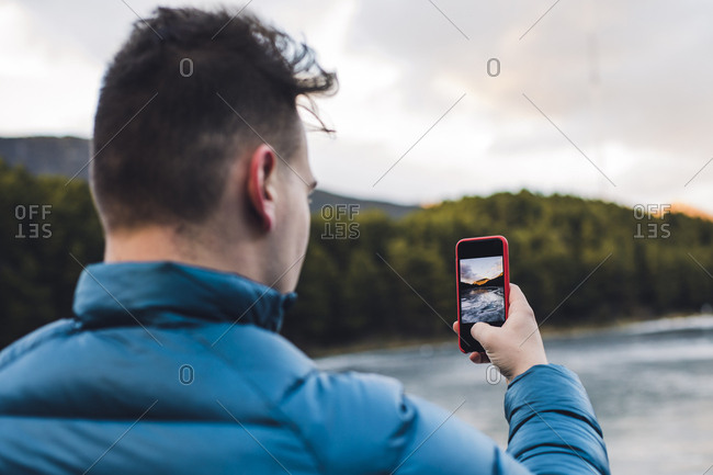 Young man taking cell phone picture at a frozen lake in winter