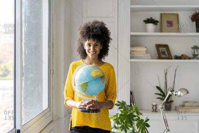 Beautiful woman holding globe- planning vacations