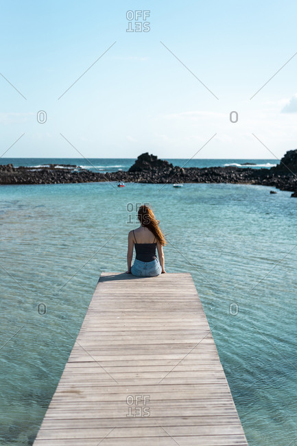 Spain- Canaray Islands- Fuerteventura- woman sitting on jetty at the sea