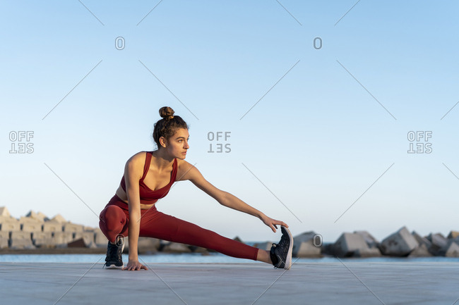 Sportive young woman during workout- stretching leg