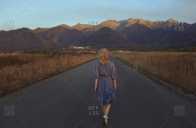 USA- California- back view of strawberry blonde woman walking on country road