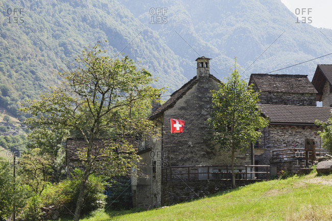 Switzerland- Ticino- Verzasca Valley- typical stone house with Swiss National Flag