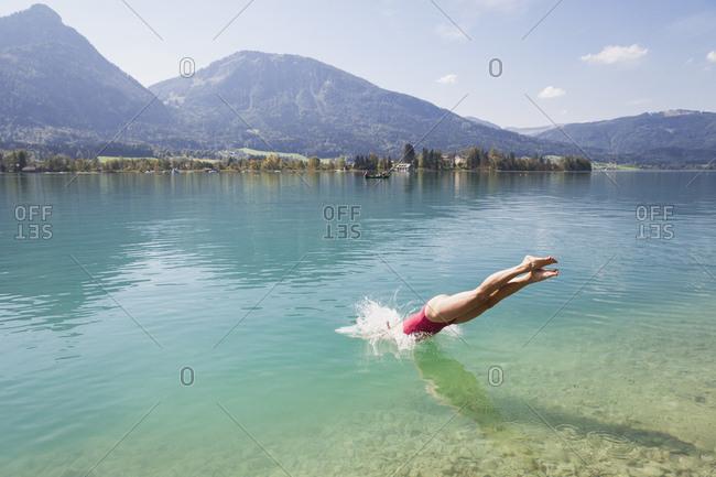 Austria- Alps- Salzburg- Salzkammergut- Salzburger Land- Wolfgangsee- woman jumping into lake