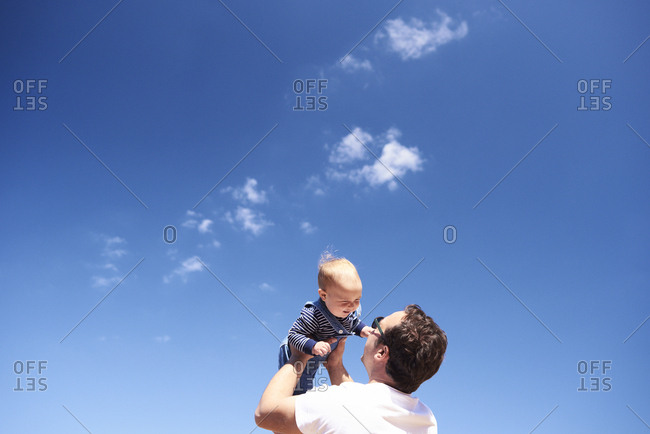 Father playing with little son on the beach