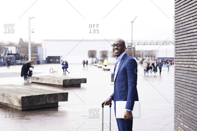 Portrait of smiling businessman with  laptop and trolley bag wearing blue suit
