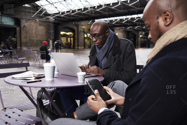 Two businessmen sitting at table of coffee shop using mobile devices