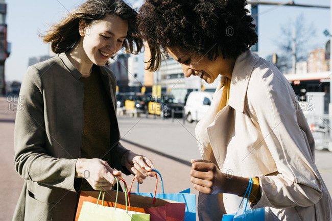 Two happy women with shopping bags in the city checking the purchase
