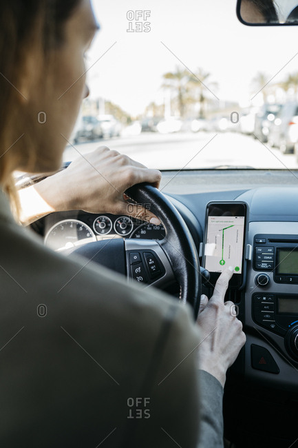 Woman driving in a car through the city using a telephone navigation app