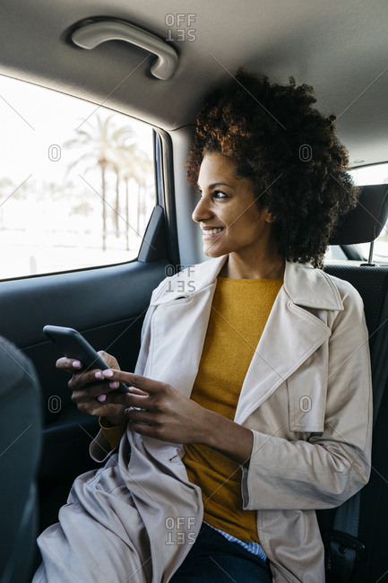 Smiling woman sitting in back seat of a car holding cell phone