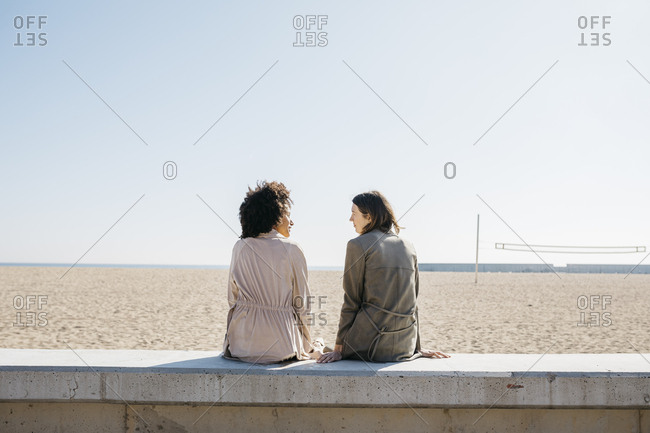 Back view of two friends sitting on the promenade enjoying leisure time