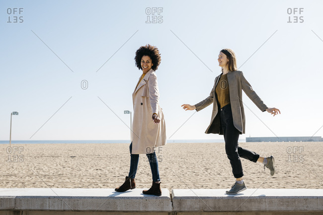 Two happy friends walking on the promenade enjoying leisure time