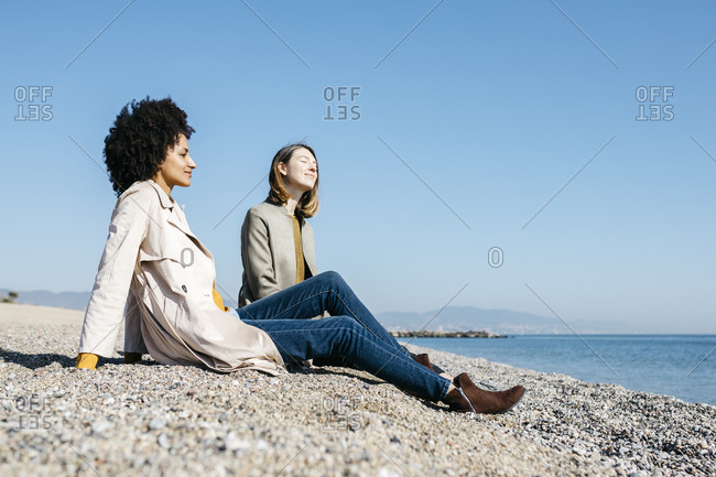 Two friends sitting on the beach enjoying leisure time