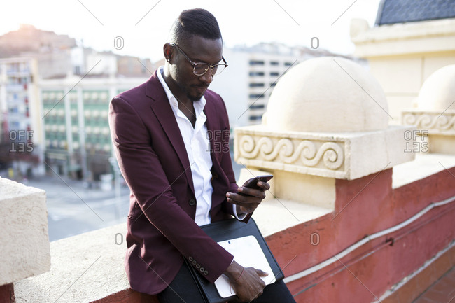 Young entrepreneur waiting on hotel terrace for his appointment- using smartphone