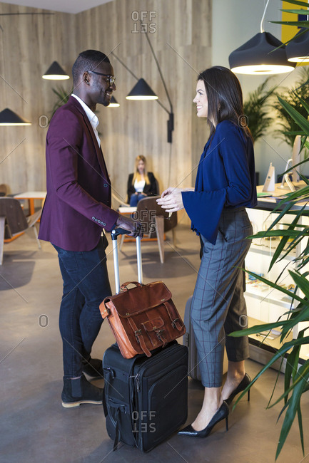 Business people waiting with luggage in hotel lobby