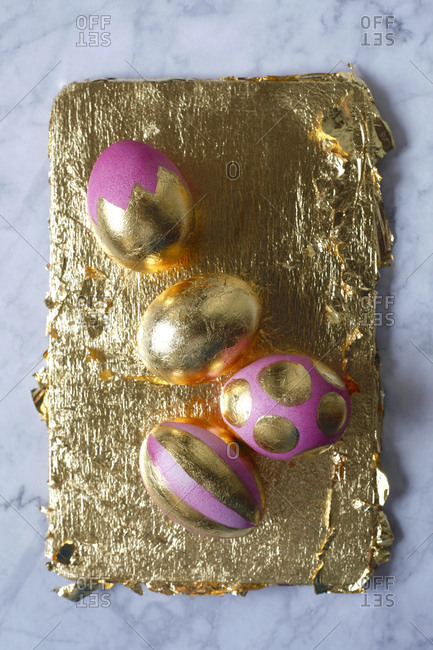 Four painted Easter eggs on golden background and marble