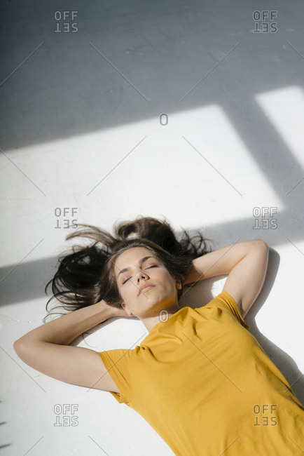 Woman lying on floor- relaxing in the sunlight