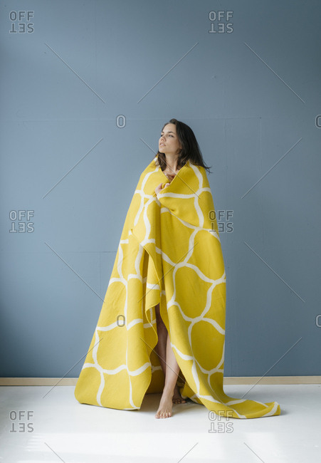 Woman standing in front of blue wall- wrapped in yellow rug