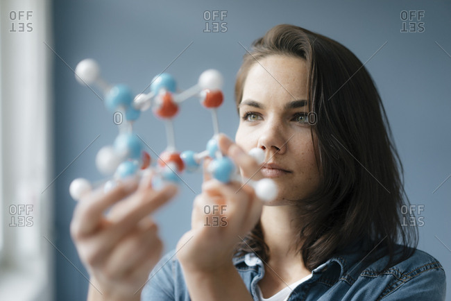 Female scientist studying molecule model- looking for solutions
