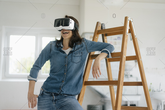 Woman with VR glasses- leaning on ladder
