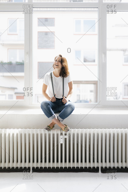 Laughing woman sitting on window sill