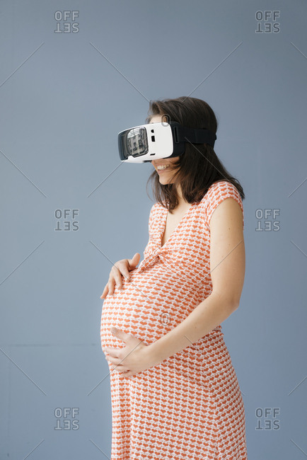 Woman pretending to be pregnant- using VR glasses