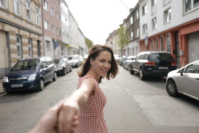 Woman walking in street- holding hand of a man