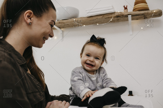 Happy mother with baby girl in baby room at home