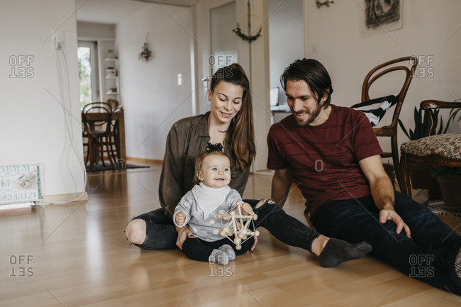 Happy family with baby girl sitting on the floor at home