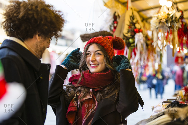 Happy young couple at Christmas market with woman trying on wooly hat