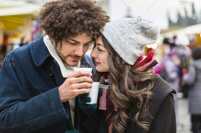 Happy affectionate young couple with hot drinks at Christmas market
