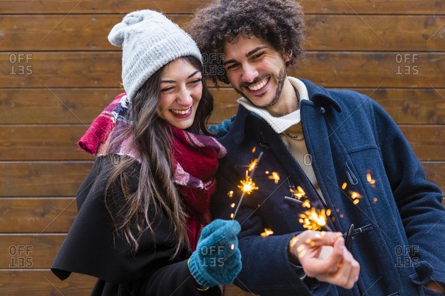 Happy young couple in winter wear holding sparklers in front of wooden wall