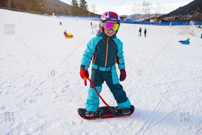 Italy- Trentino-Alto Adige- happy boy on small snowboard on piste