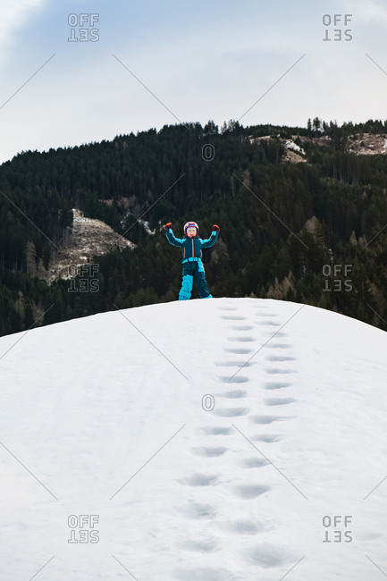 Italy- Trentino-Alto Adige- happy boy standing on a hill in winter