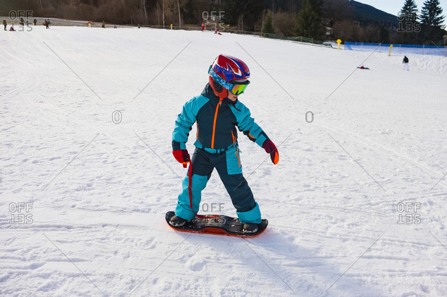 Italy- Trentino-Alto Adige- boy riding on small snowboard on piste