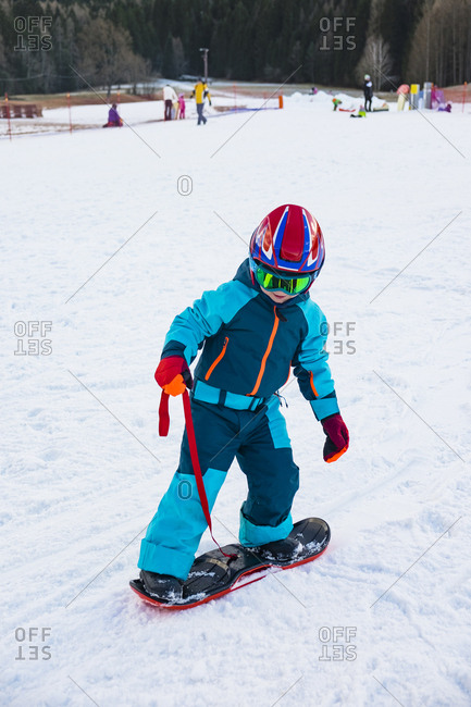 Italy- Trentino-Alto Adige- boy riding on small snowboard on piste