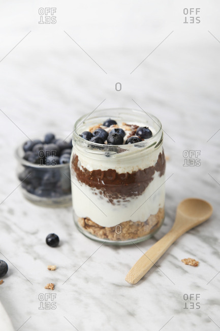 Jar of chia pudding parfait with chocolate and yoghurt with blueberries and granola