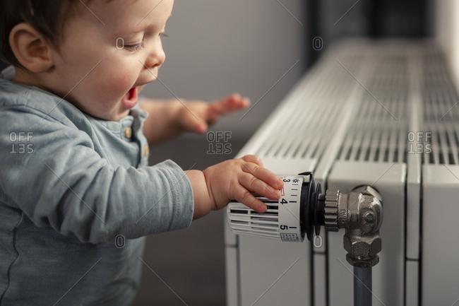 Excited baby boy playing with thermostat of heater