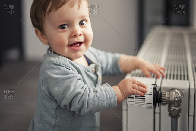 Portrait of smiling baby boy playing with thermostat of heater