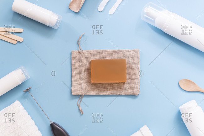 Kit to make your own cosmetics- cream- gunny bag and soap on blue background
